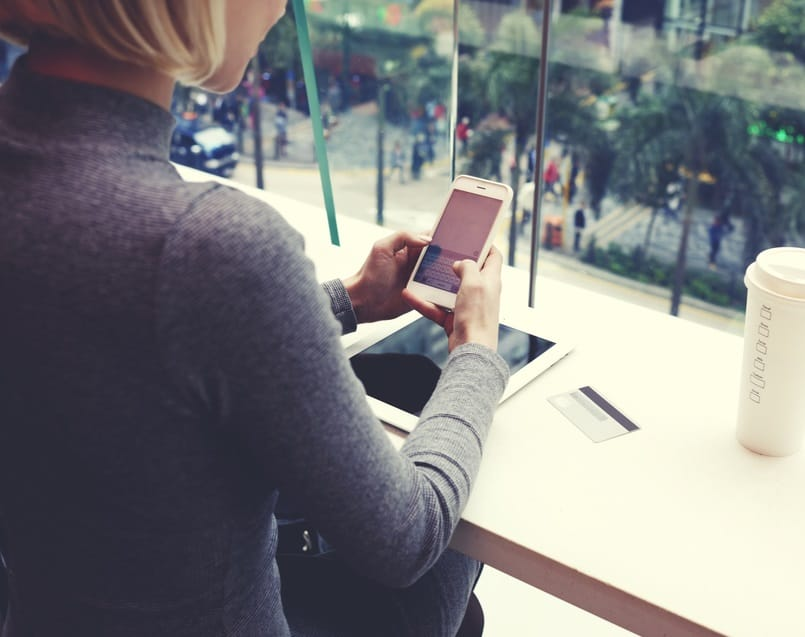 Woman browsing car leasing deals on mobile phone