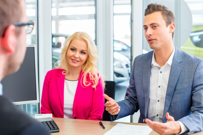 Couple arranging car finance with car dealer